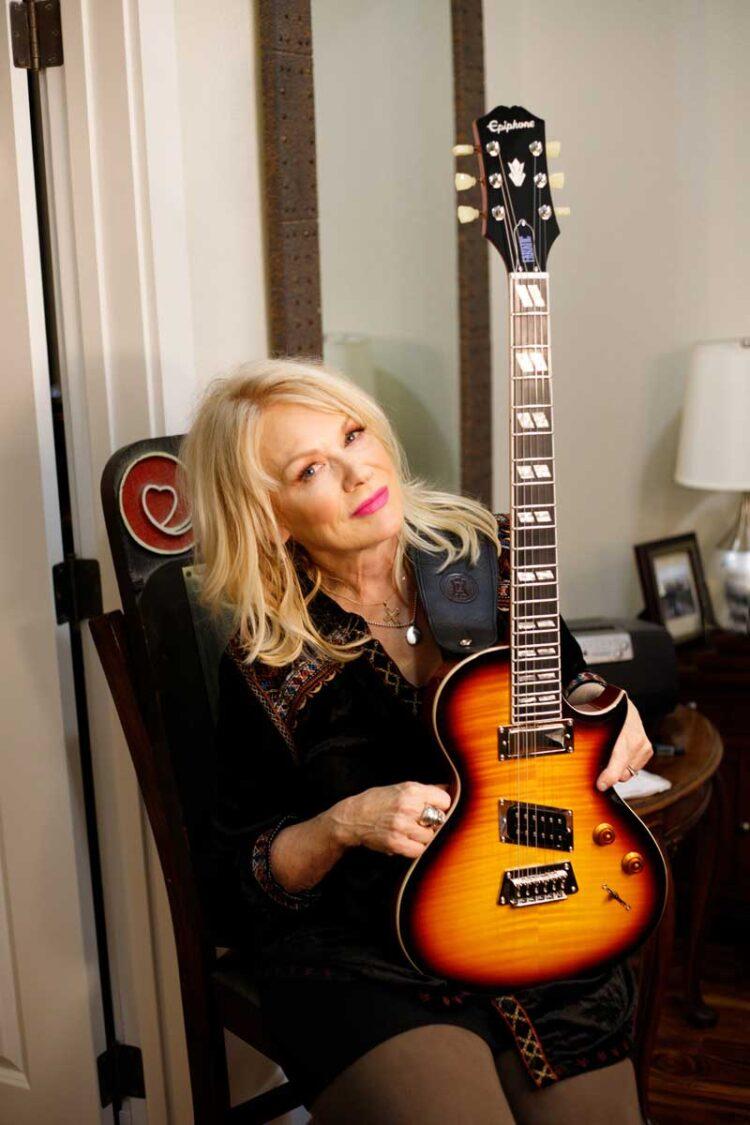 Photo of Nancy Wilson, and her custom designed Epiphone Nancy Wilson Fanatic guitar